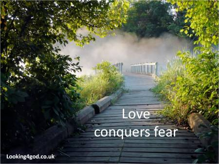 Love conquers fear (photo of wooden path over misty bridge into the unknown) surrounded by greenery
