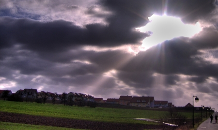 The storm in me Photo of dark, cloudy sky, with patches and streaks of light bursting forth over housing estate and green fields