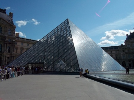 Louvre: Old and new, monstrosity or triumph?  Photo of the glass pyramid sat next to ancient buildings of the Louvre in Paris, France