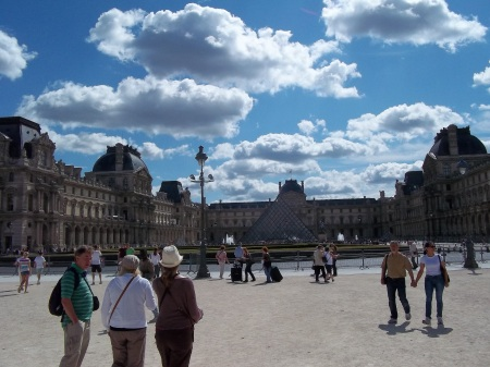Louvre from a distance photo by Michelle Sherlock glass pyramid, tourists, ancient buildings, gorgeous blue sky and fluffy white clouds
