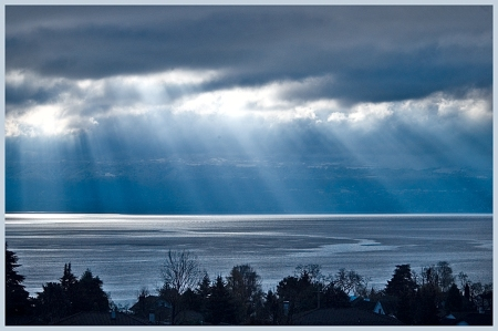 Dwelling with God poem by Michelle Sherlock  Photo of angel rays through clouds onto water and land below