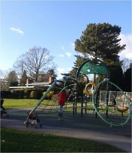 Photo of children at play park with bright blue sky and trees in the background