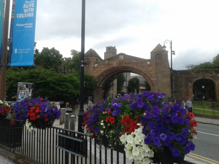 Photo of blue, red and white flowers (petunias) in baskets between Chester's Roman ampitheatre and Chester's wall and gate