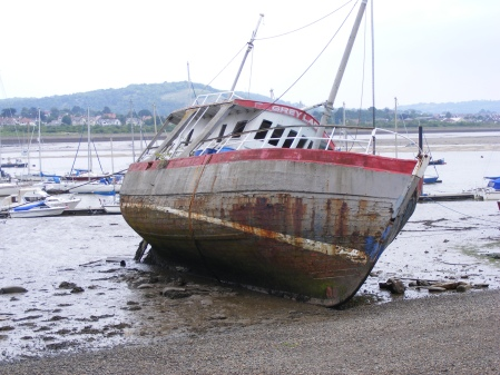 Photo of rusty sailing ship called the Grey Lady on its side in the mud