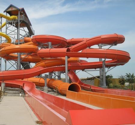 Photo of very tall orange slide tubes like an over sized helter skelter slide