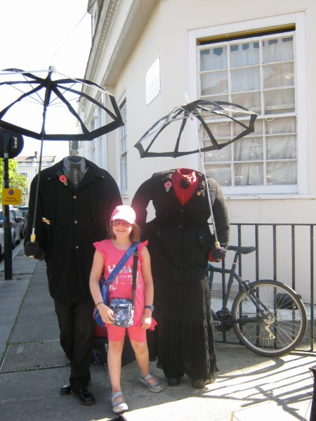 Photo of two larger than life street artists with their heads covered by dark suit of clothes