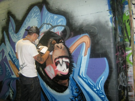 Photo of graffiti artists creating picture of an ape with sharp teeth against blue and purple background