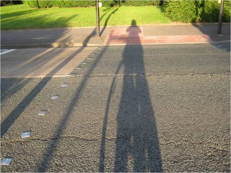 Photo of the shadow of a cyclist stretching across the whole road