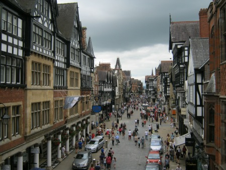 Photo of historic town of Chester with black and white painted fronts with different floors jutting out in layers and people dashing around