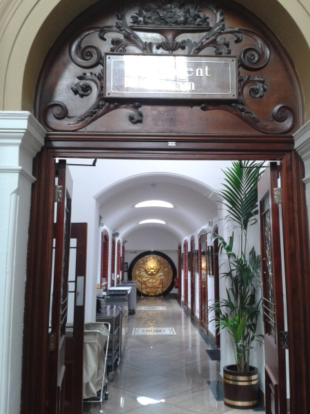 Marble competes with historic wooden decoration, green foliage lightens walls, while a corridor of archways is made meaningful by a carved wooden disc of a dragon in the distance