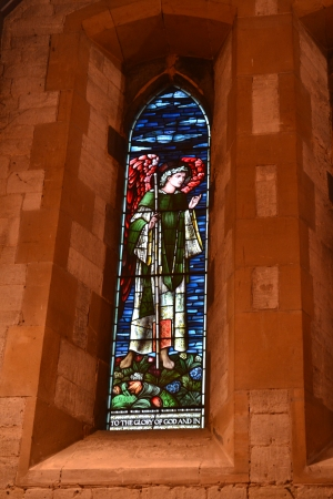 Photo of winged stained glass angel standing against blue sky