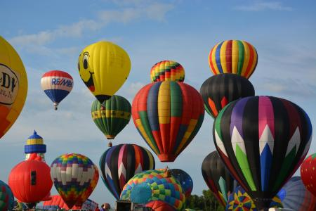 Photos of multi-coloured hot air balloons rising, including bright yellow smiley one
