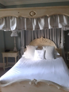 Photo of a 4 poster bed with Mr and Mrs cushions
