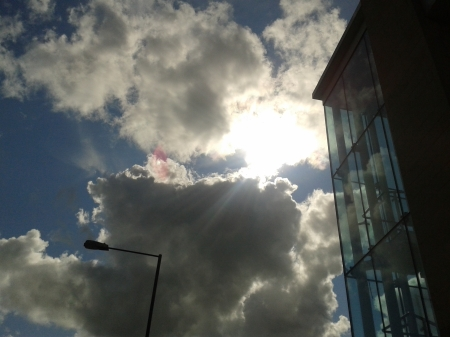 Photo of building with glass rectangles and stairs showing zig zag lines and lamppost as a zig zag against sun shining through clouds