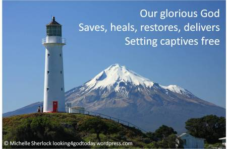 photo of lighthouse with snowy mountain tops in the background