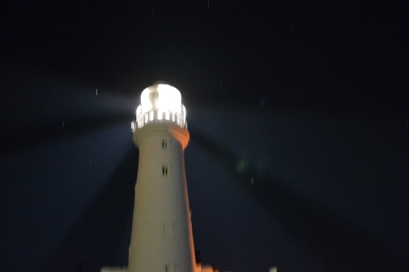 Flamborough Lighthouse at night shining in at least 4 directions at one