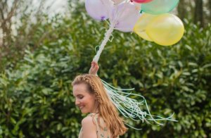 Girl smiling, dancing with balloons from Mercy Ministries